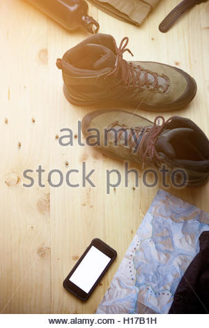 Top view Trekking Equipment ,trekking shoe, mobile phone ,bottle ,pant,gps watch and map on wooden plate ,cross - Stock Photo