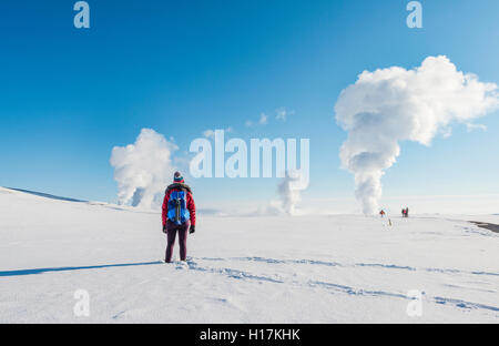 Woman standing in snow, rising steam, Hverarönd, also Hverir or Namaskard, geothermal area, North Iceland, Iceland - Stock Photo
