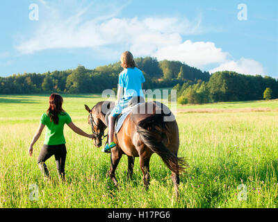 Horseback Riding Lessons - Woman Leading a Horse with a Boy in Saddle - Stock Photo