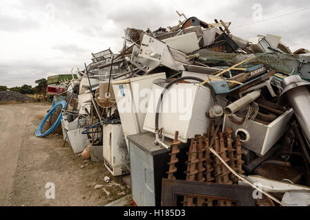 Piles of scrap metal and kitchen goods collected at a scrap yard for recycling - Stock Photo