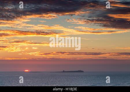 Sun Breaks Horizon Looking Across Inner Sound towards Farne Islands - Stock Photo