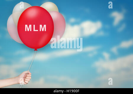 Hand Holding MLM or Multi level marketing Balloon with sky blurred background - Stock Photo