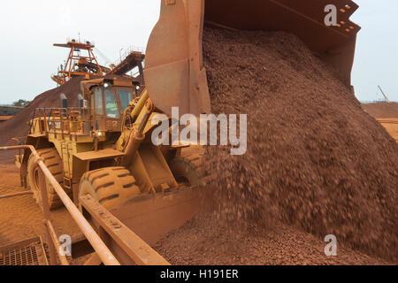 Front end loader loading hopper with lump iron ore from reclaimed stack behind. Ore then passes onto conveyor belt - Stock Photo