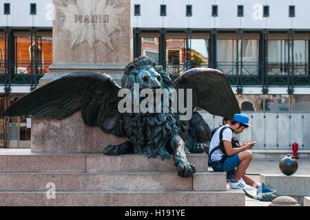 Venezia. 2016. Young venetians on a statue in Campo Manin. ©Simone Padovani - Stock Photo