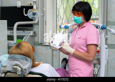 Female dentist examining patients teeth in the dentists chair - Stock Photo