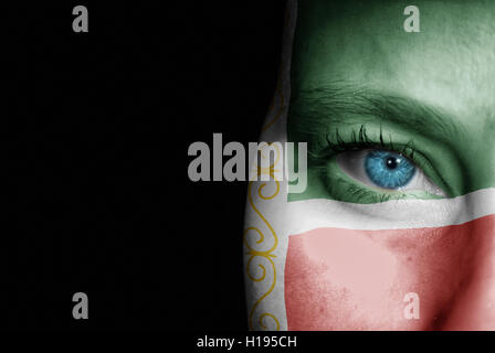 A young female with the flag of Chechen Republic painted on her face on her way to a sporting event to show her - Stock Photo
