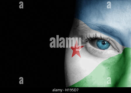 A young female with the flag of Djibouti painted on her face on her way to a sporting event to show her support. - Stock Photo