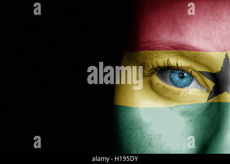 A young female with the flag of Ghana painted on her face on her way to a sporting event to show her support. - Stock Photo