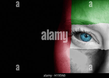 A young female with the flag of United Arab Emirates painted on her face on her way to a sporting event to show - Stock Photo
