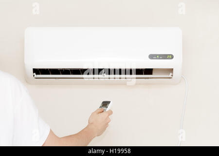 One man hand using remote air Conditioner indoors unit - Stock Photo