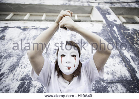 Bloody killer mask with knife threat and fear - Stock Photo