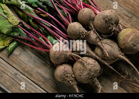 Young beets with green leaves on wooden background - Stock Photo