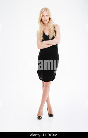 Full length portrait of a beautful woman in black dress standing with arms folded isolated on a white background - Stock Photo