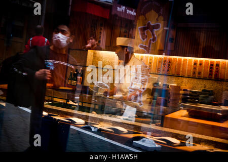 Pedestrians walk past a sushi bar in Tokyo, Japan - Stock Photo