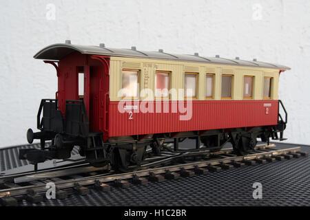 Red plastic miniature model of a train wagon. Train wagon toy. - Stock Photo