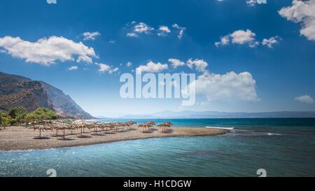 Straw umbrella on a sandy beach in Greece. - Stock Photo