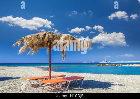 Straw umbrella on a sandy beach in Greece. Beach chairs with umbrellas on a beautiful beach in Crete island. - Stock Photo