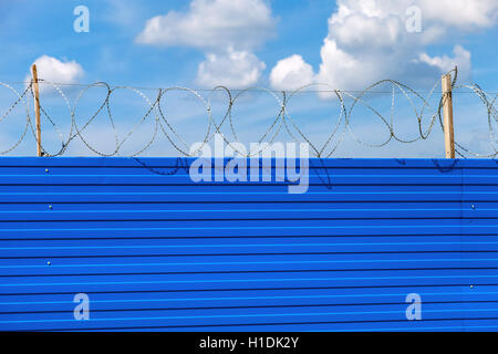 Barbed wire on the fence against a blue sky background. Restricted area - Stock Photo