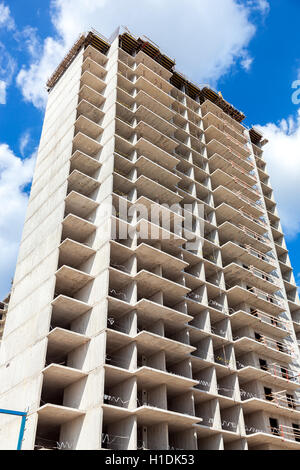 New tall apartment building under construction against blue sky background - Stock Photo