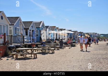 couple in hand walking in front of beach huts on Mudeford sandbanks, Hengistbury head in dorset england - Stock Photo