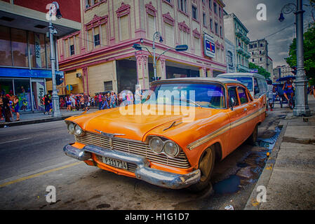 HAVANA, CUBA - 4 DEC, 2015. Orange vintage classic American car, commonly used as private taxi parked in Havana - Stock Photo