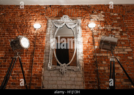 Old ornate frames on mirror glas hanging on a brick wall. - Stock Photo