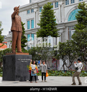 Tourists take photo in front of Ho Chi Minh Statue. Ho Chi Minh City, Vietnam. - Stock Photo