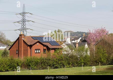 House in proximity to pylon, Wales, UK - Stock Photo