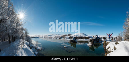 Hiker with arms in the air, overlooking Lake Mývatn in winter, Iceland - Stock Photo