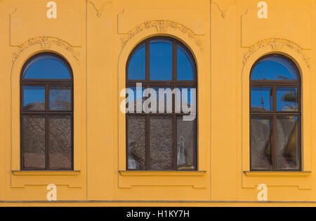 Ornate yellow facade of an old building with three windows with archs, reflecting a blue sky and a roof a the oposite - Stock Photo