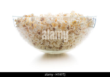 Tasty salted popcorn in big glass bowl isolated on white background. - Stock Photo