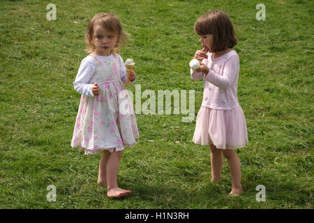 Summer, UK. Two little girls enjoying icecreams while barefoot on the grass - Stock Photo