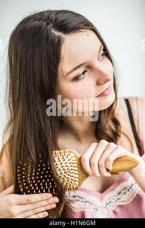 Teenage girl brushing her hair. - Stock Photo