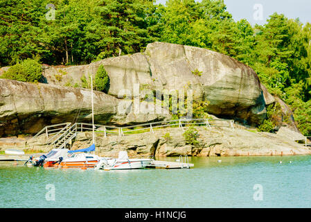 Askeron, Sweden - September 9, 2016: Environmental documentary of small marina with cliffs in background. Boats - Stock Photo