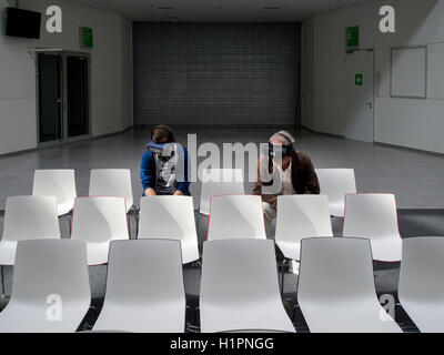 The future of visual entertainment, two men wearing VR glasses in boring and sterile environment. Cologne, Germany - Stock Photo
