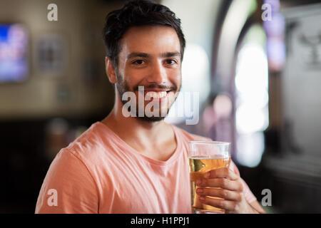 happy man drinking beer at bar or pub - Stock Photo