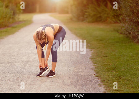 Young woman limbering up before training doing exercises to stretch her muscles on a country path in morning light - Stock Photo
