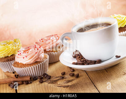cup of coffee and cupcakes on the wooden background. - Stock Photo