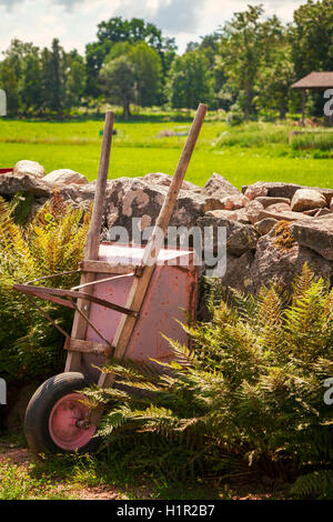 Image of a wheelbarrow against a natural stone wall in a rural setting. - Stock Photo