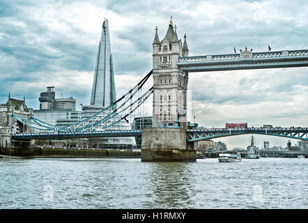 Tower bridge and red London bus with The Shard in background, seen from the river Thames - Stock Photo