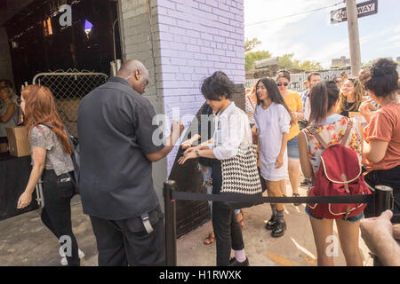Security checks hand stamps of attendees in the Bushwick neighborhood of Brooklyn prior to allowing them to enter - Stock Photo