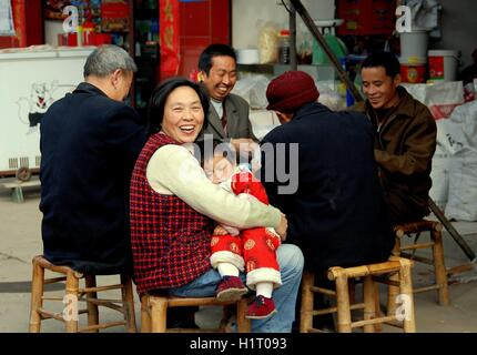 Li'an Village, China:  Grandmother holding her grandson sitting next to four men playing cards - Stock Photo