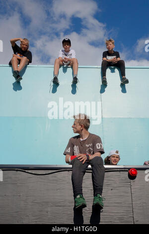 Parkour kids sit and relax on a edge of a building's terrace. - Stock Photo