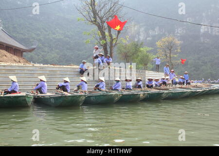 Ninh Binh, Vietnam - March 29, 2010: Ferrymen are waiting for tourists to visit the Trang An Eco-Tourism Complex, - Stock Photo