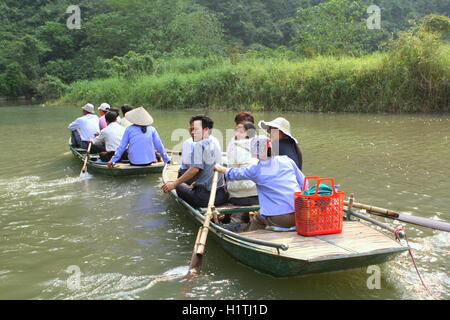 Ninh Binh, Vietnam - March 29, 2010: Ferrymen are taking tourists to visit the Trang An Eco-Tourism Complex, a complex - Stock Photo