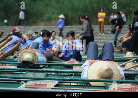 Ninh Binh, Vietnam - March 29, 2010: Ferrywomen are waiting for tourists visiting the Trang An Eco-Tourism Complex, - Stock Photo