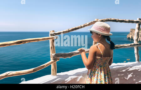 Little girl standing on balcony looking to the sea - Stock Photo