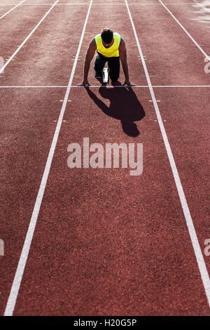 Runner on tartan track in starting position - Stock Photo