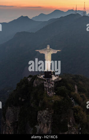 Christ the Redeemer statue on Corcovado Mountain looking toward the mountains at sunset in Rio de Janeiro, Brazil. - Stock Photo