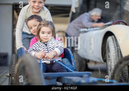 Boy pushing two little girls in go-kart - Stock Photo